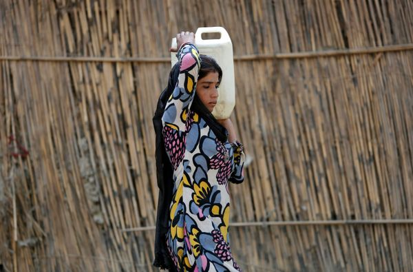 A girl carries a can filled with drinking water in New Delhi.