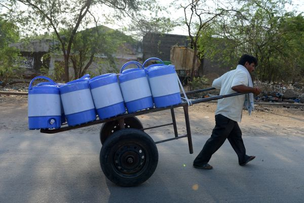 A villager carries drinking water containers in Chandampet Mandal.