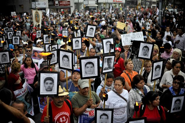 Protesters march in Mexico City on April 26, 2016, carrying the portraits of the 43 students who...