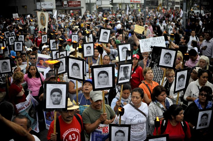 Protesters march in Mexico City onApril 26, 2016, carrying the portraits of the 43 students who have been missing since