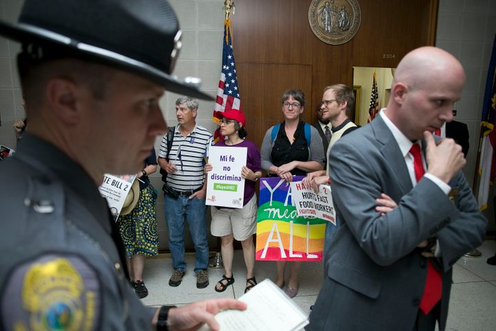 Opponents of the anti-LGBT bill passed by the North Carolina legislature stage a protest outside of House Speaker Tim Moore's