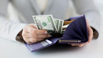 business, finance, saving, banking and people concept - close up of woman hands with wallet and us dollar money