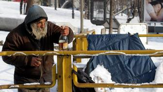 A homeless man holds a bottle of alcohol near an underground station in downtown Milan February 10, 2012, as sub-freezing winter weather temperatures continue in Europe.          REUTERS/Stefano Rellandini   (ITALY  - Tags: ENVIRONMENT SOCIETY POVERTY)