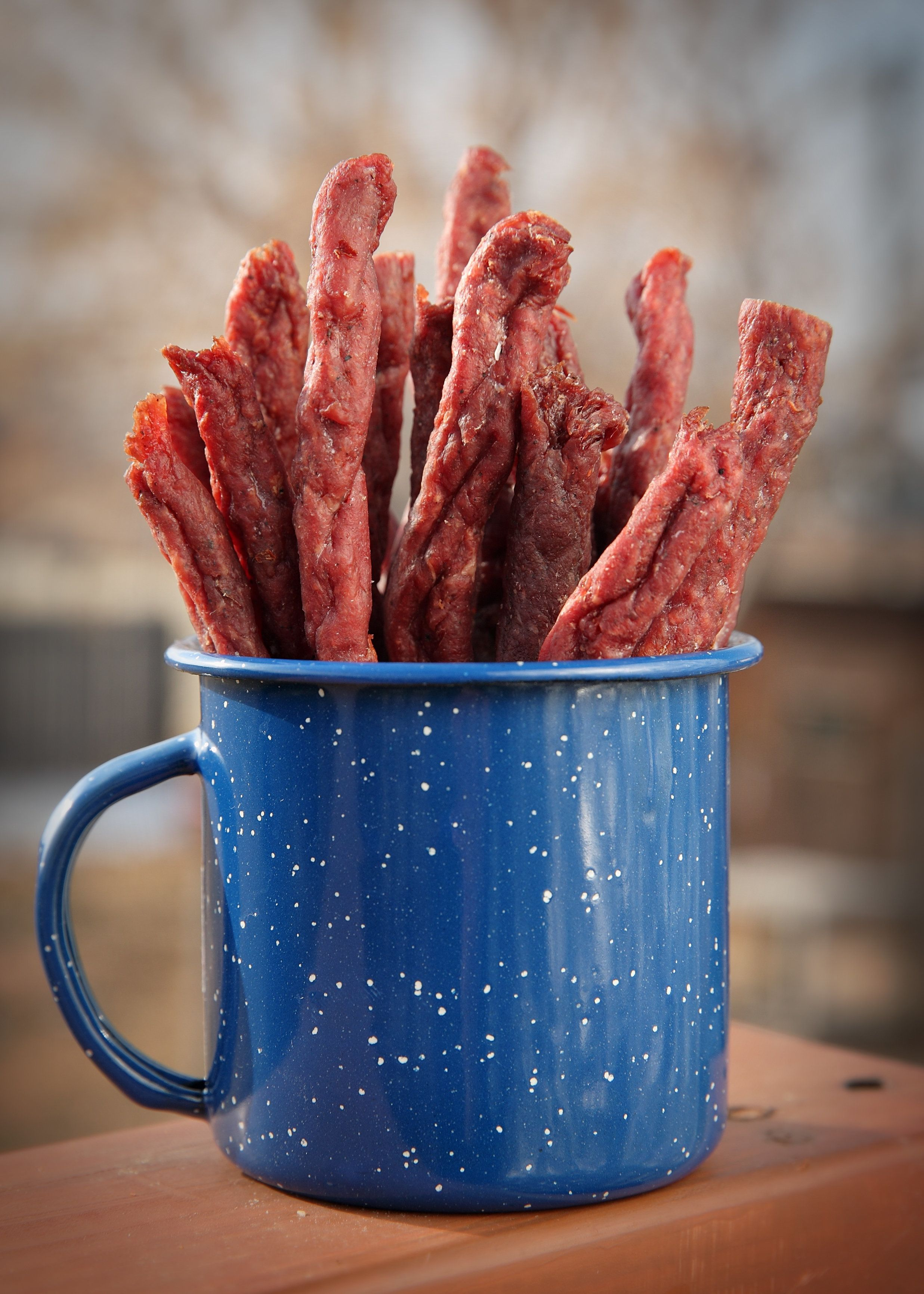 close-up mug of homemade jerky in outdoor setting
