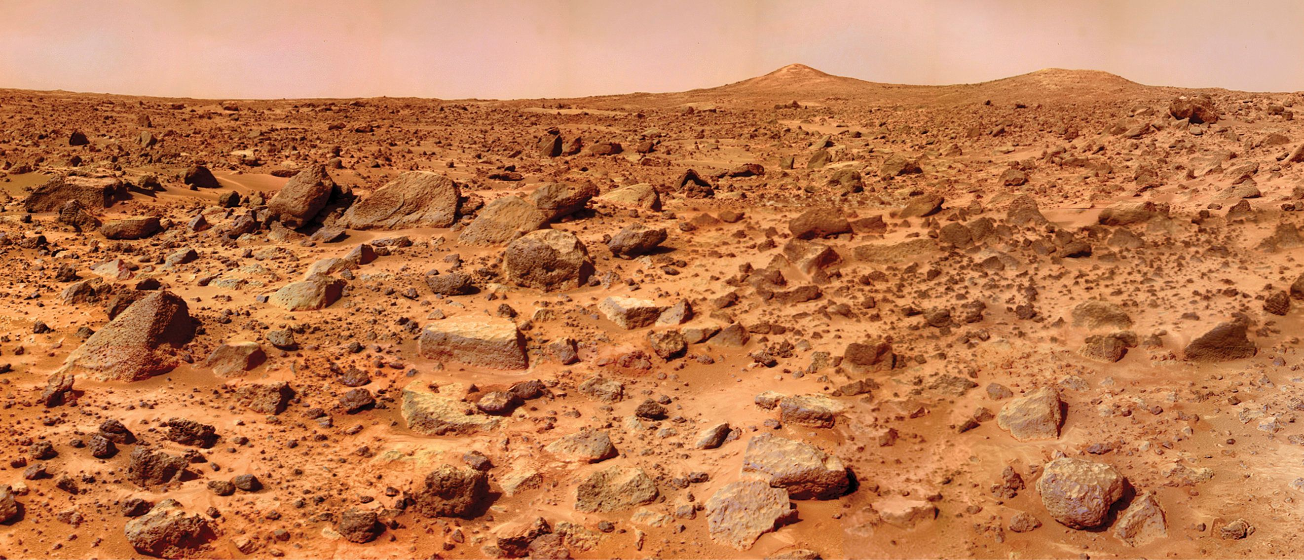A composite of several images taken by the Mars Pathfinder lander shows the boulder-strewn surface of Mars at Chryse Planitia. In the distance are two hills dubbed 'Twin Peaks,' which are about 100 feet (30 meters) tall.