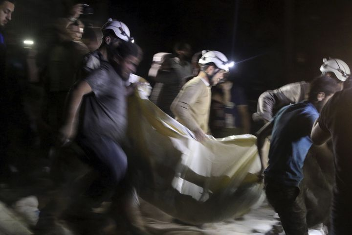 Civil defense members carry a casualty after an airstrike at a field hospital in Aleppo, Syria.