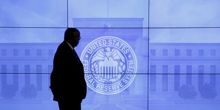 A security guard walks in front of an image of the Federal Reserve following the two-day Federal Open Market Committee (FOMC)