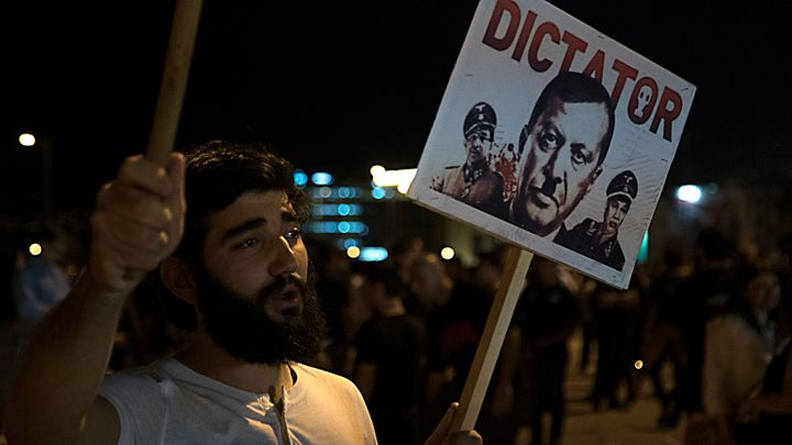 An attendee of the Armenian Genocide commemoration in downtown Beirut holds a placard depicting Turkish President Recip Teyyi
