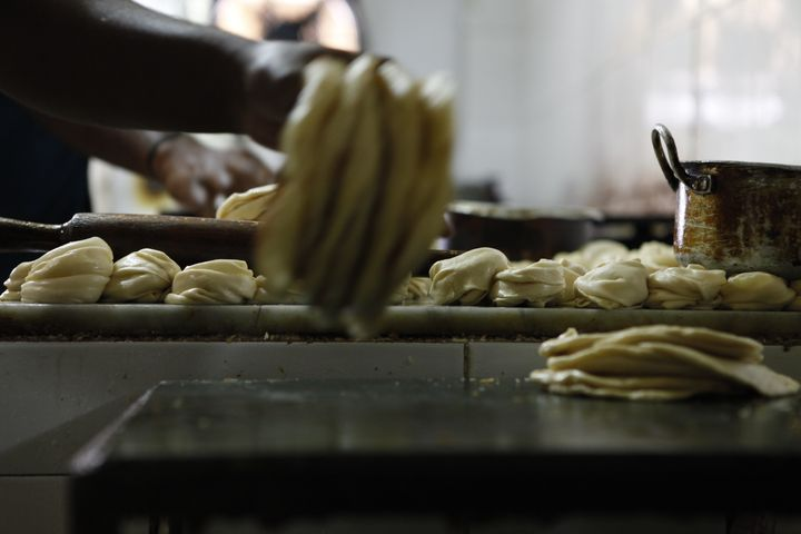 An employee at the New Indo-Lankan Restaurant prepares rotis for customers in the midst of a Sunday lunch rush.