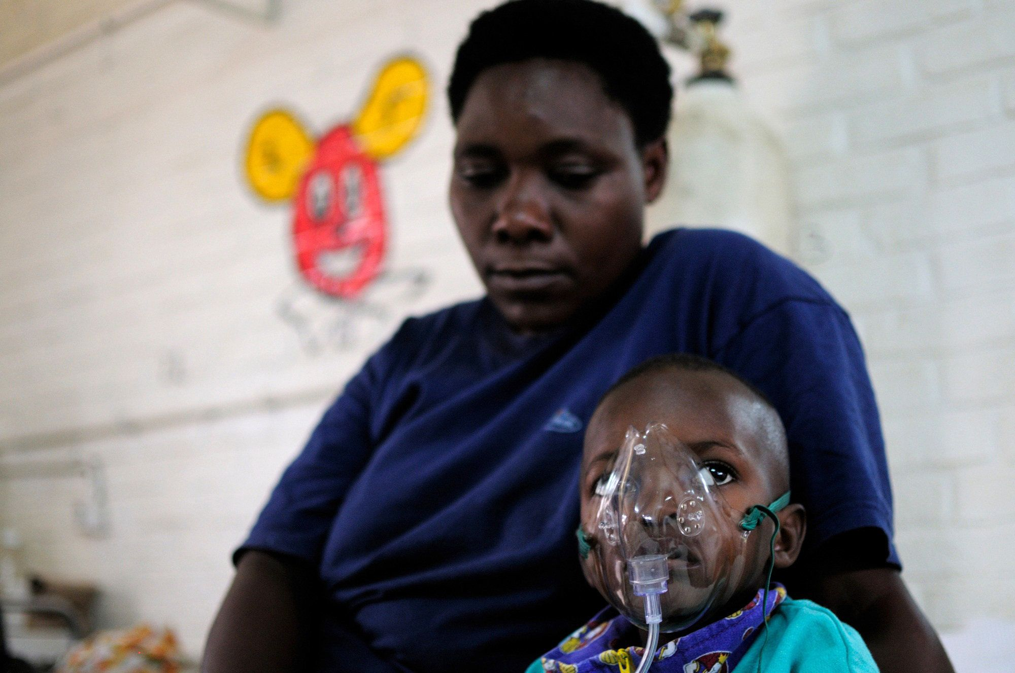 TO GO WITH by Helen Vesperini Yves Twemerimana, 3, wears an oxygen mask in a bed at the Kigali Central University Hospital in Kigali, as he is tended to by Dr Narcisse Muganga for a severe case of pneumonia on September 1, 2010. With big strides made against both malaria and pneumococcal disease, Rwanda is on track to meet UN Millennium Development Goal no 4, the reduction of child mortality, officials say. 'Rwanda is one of the few countries in Africa that stands a chance of reaching the MDG targets if the current rhythm is maintained,' said Lamine Cisse Sarr, World Health Organisation representative to Rwanda.        AFP PHOTO/HO/SHANON JENSEN (Photo credit should read Shannon Jensen/AFP/Getty Images)