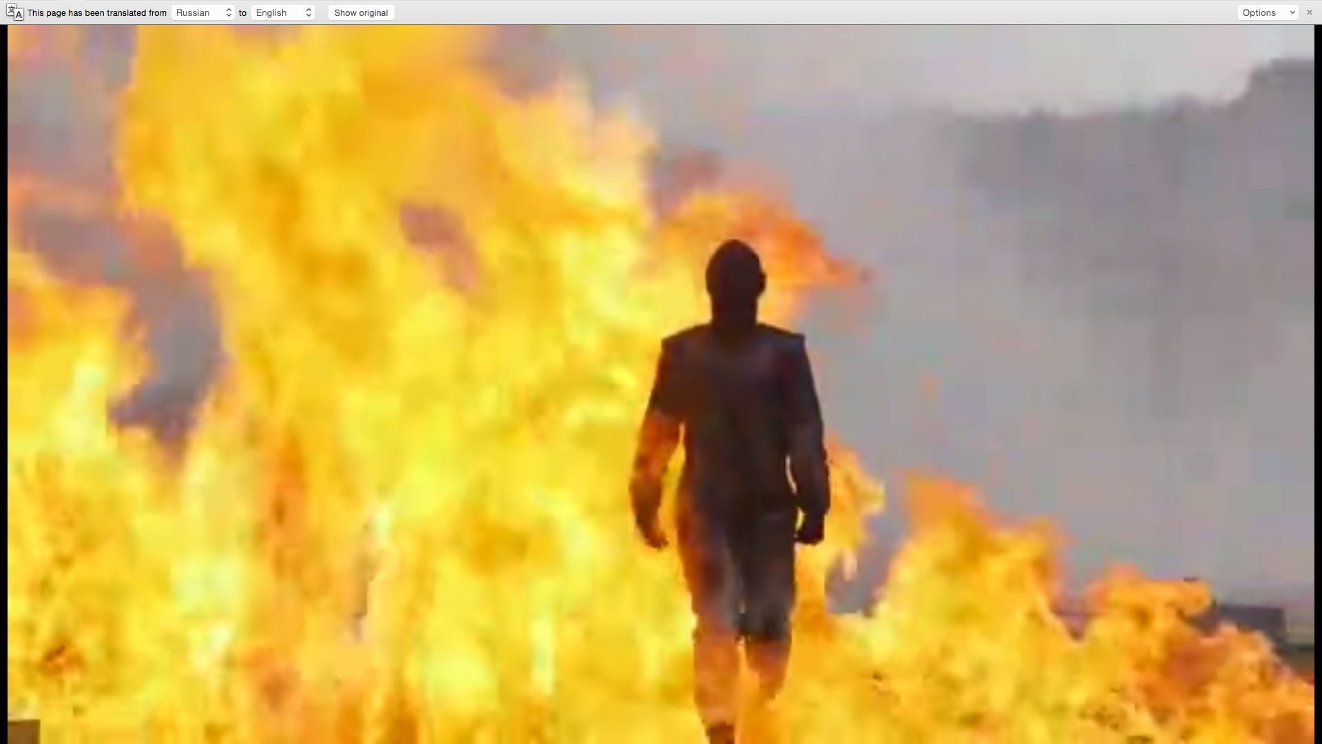 A woman wearing a fire-proof suit is seen walking through a field of explosives.