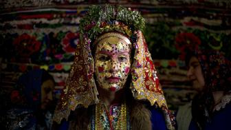Emilia Pechinkova, a 24-years-old Bulgarian Pomak (Bulgarian speaking Muslims) bride poses for a photograph following the 'gelina' or face painting ceremony carried out by female guests and relatives in preparation for her three-day wedding ceremony in the village of Draginovo, 100 kms southeast of Sofia on April 22, 2016. Bulgaria's Muslim population is one of the highest in the European Union. During the Communist regime religious rituals were not tolerated, and Muslims were forced to abandon wearing their traditional wedding outfits. Recently, more young Pomak women want to include traditional wedding customs that were forbidden during the regime, regardless of their secular lifestyles and the high cost of such a wedding.   / AFP / NIKOLAY DOYCHINOV        (Photo credit should read NIKOLAY DOYCHINOV/AFP/Getty Images)