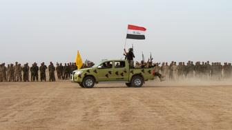 Members of the Iraqi security forces drive holding their national flag as their comrades line up during a training in a camp near Fallujah, in Iraq's Anbar province, on April 25, 2016.    Iraqi forces have largely cut off access to Fallujah, while the Islamic State (IS) group is preventing residents from leaving the city.   / AFP / MOADH AL-DULAIMI        (Photo credit should read MOADH AL-DULAIMI/AFP/Getty Images)