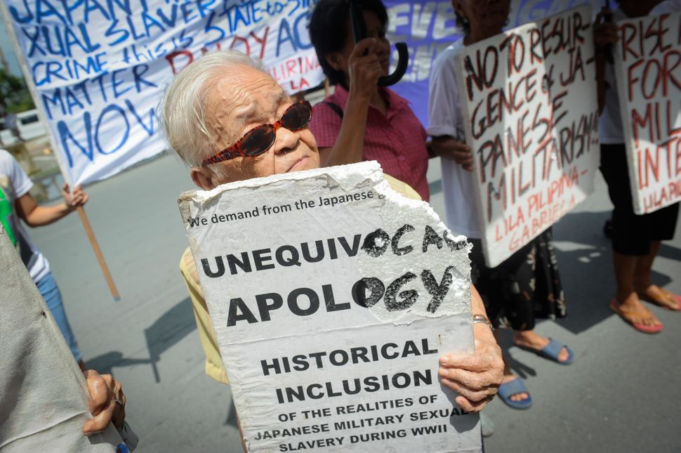 Remedios Pecson holds a sign at a protest in front of the Japanese Embassy on Aug. 14, 2015. Pecson, then 80 years old,