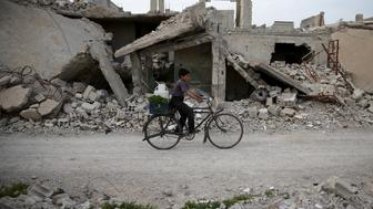 A boy rides a bicycle near rubble of damaged buildings in the rebel held besieged town of Douma, eastern Damascus suburb of Ghouta, Syria March 19, 2016. REUTERS/Bassam Khabieh