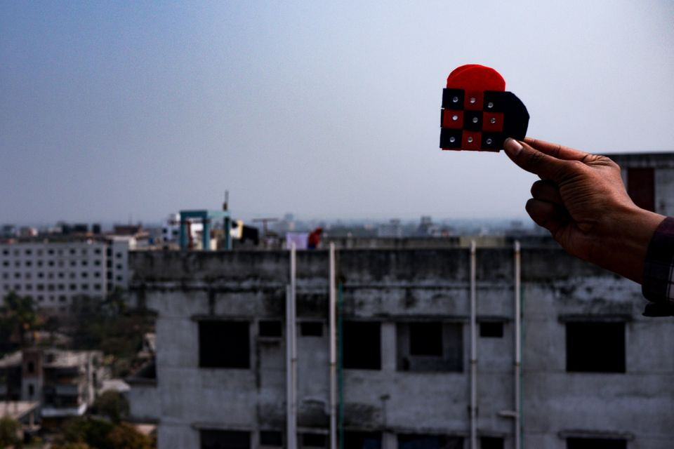 A heart, symbolizing the strength and resilience of Bangladesh's garment factory workers, against Dhaka's city skyline. Many