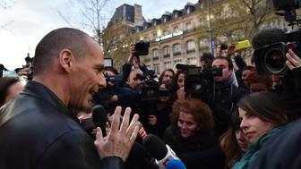 Greece's far-left former finance minister Yanis Varoufakis (L) speaks to journalists as he joins protesters taking part in the 'Nuit Debout' (Up All Night) movement against the government's labour reforms, on the Place de la Republique in Paris, on April 16, 2016. The Nuit Debout or 'Up All Night' protests began in opposition to the Socialist government's labour reforms seen as threatening workers' rights, but have since gathered a number of causes, from migrants' rights to anti-globalisation. / AFP / ALAIN JOCARD        (Photo credit should read ALAIN JOCARD/AFP/Getty Images)