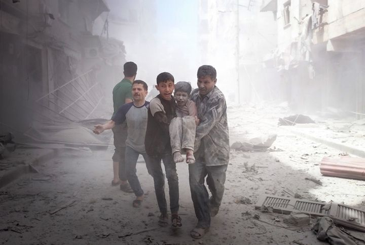 People carry an injured boy after airstrikes on Aleppo on Thursday. Nearly 250 civilians have died in nine straight days of b