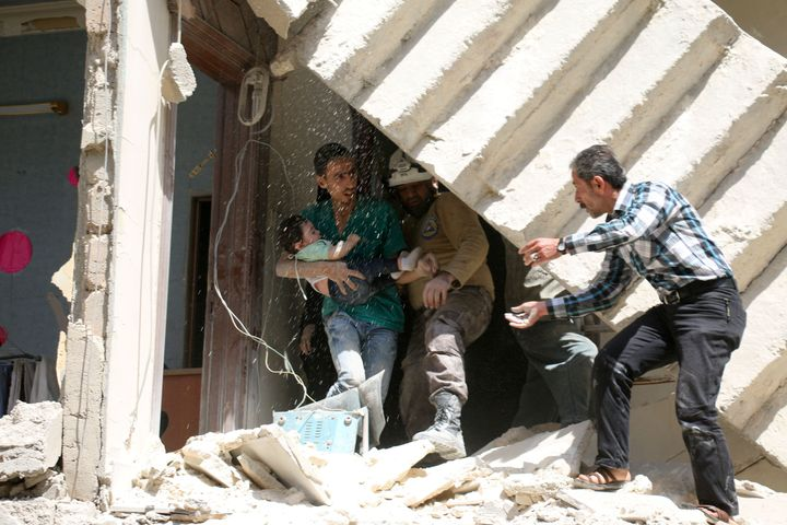 Syrians evacuate a toddler from a destroyed building in Aleppo on Thursday. Taking full control of the city would be a major