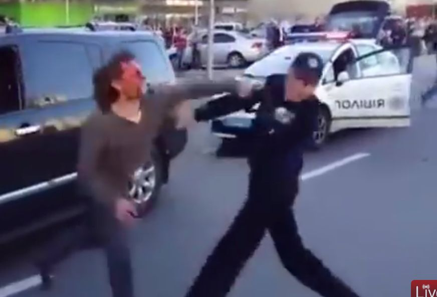 Yacheslav Oliynyk tries to punch an officer after being pulled
