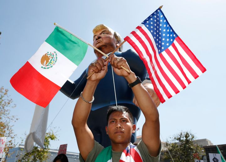 Valente Martinez, 22, marches with Mexican and U.S. flags under an inflatable effigy of Republican presidential candidate Don