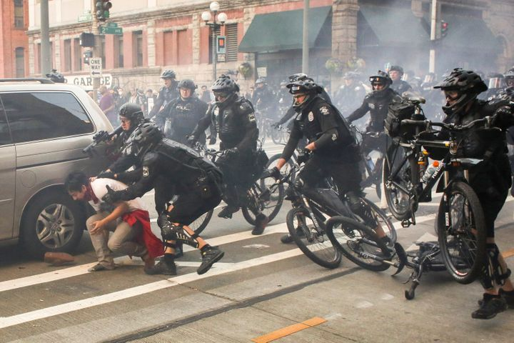 Police officers detain a protester during anti-capitalist protests following May Day marches in Seattle, Washington.