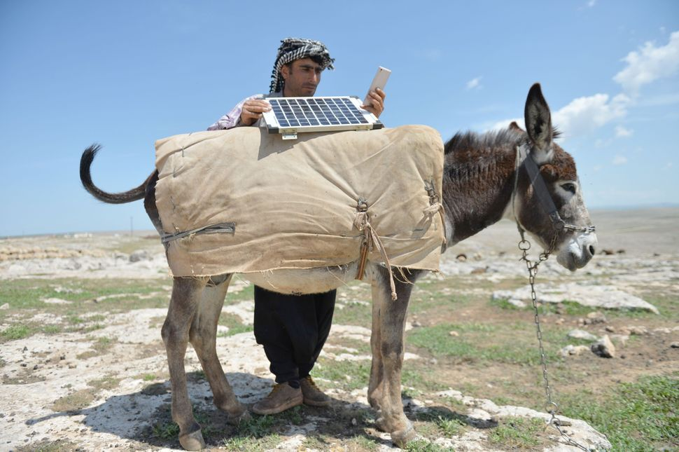 A shepherd in Turkey charges his phone using solar panels.