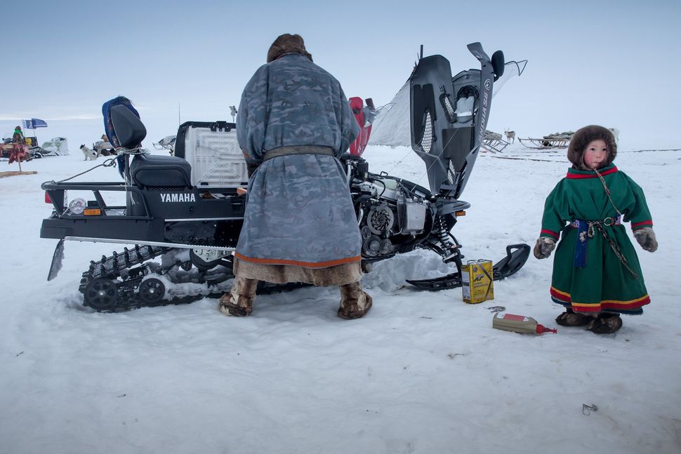 A Nenet man prepares his snow motorcycle, 150 km from the town of Salekhard, Yamalo-Nenets Autonomous Okrug, in Russia on Apr