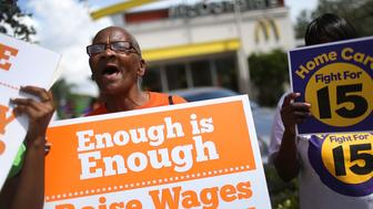 FORT LAUDERDALE, FL - SEPTEMBER 10:  Laura Rollins joins with others to protest in front of a McDonald's restaurant in support of a $15 an hour minimum wage on September 10, 2015 in Fort Lauderdale, Florida.  Seattle, San Francisco and Los Angeles are among cities that have adopted a $15 an hour minimum wages.  (Photo by Joe Raedle/Getty Images)
