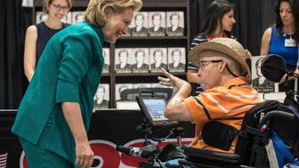 Former US Secretary of State Hillary Clinton greets a man in a wheelchair as she signs her new book 'Hard Choices' in Arlington, Virginia, outside Washington, on June 14, 2014. Clinton is widely thought to be mulling a run for the 2016 presidential election.   AFP PHOTO/Nicholas KAMM        (Photo credit should read NICHOLAS KAMM/AFP/Getty Images)