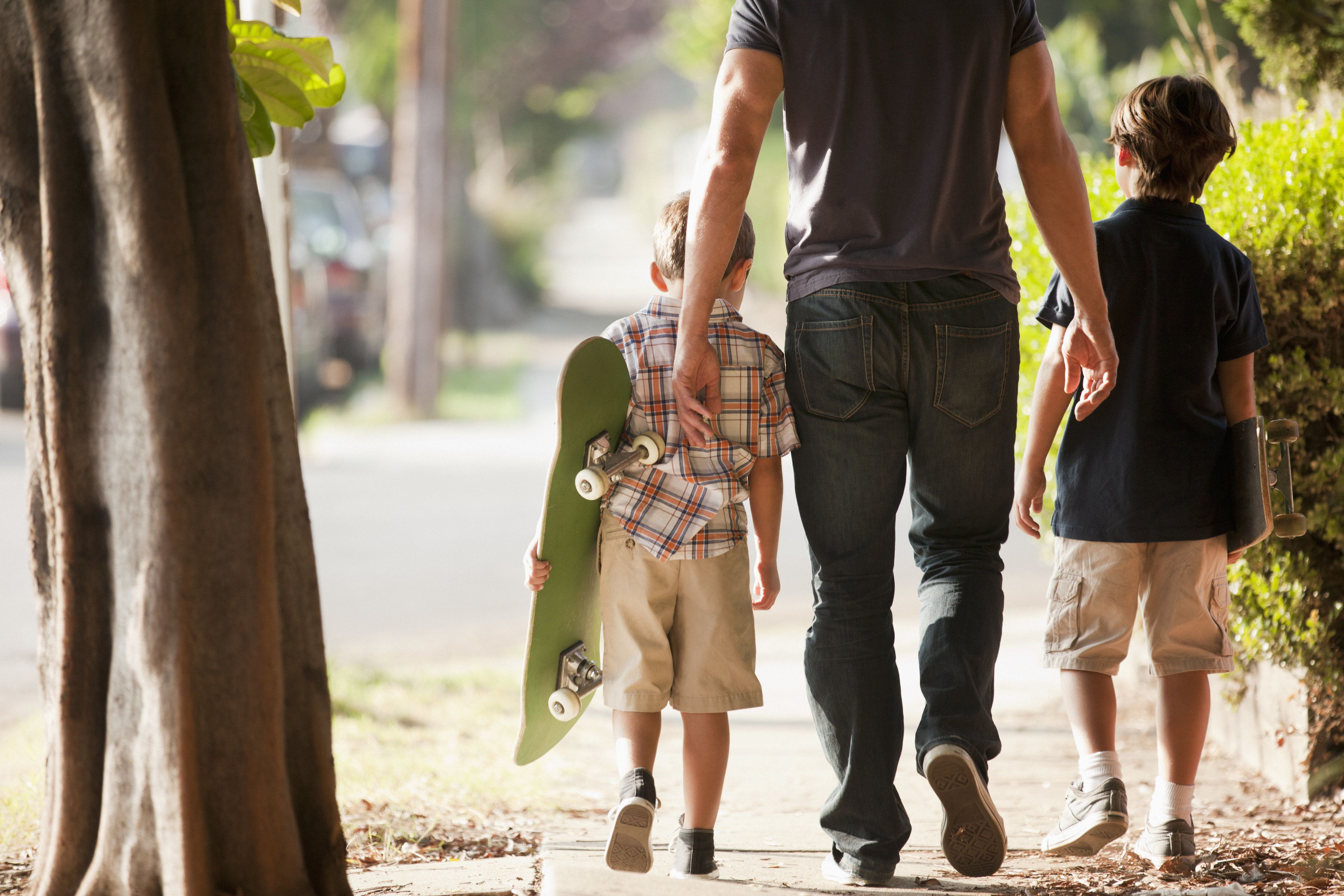 Father and sons walking on suburban street