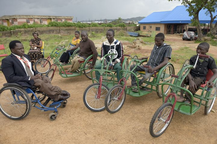 Founder of Beautiful Gate Handicapped People's Centre Ayuba Gufwan (L) speaks to handicapped recipients of his new wheelchair