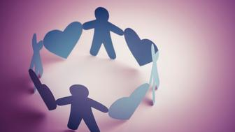 Cut out people and heart shapes linked, as a symbol of a caring community.