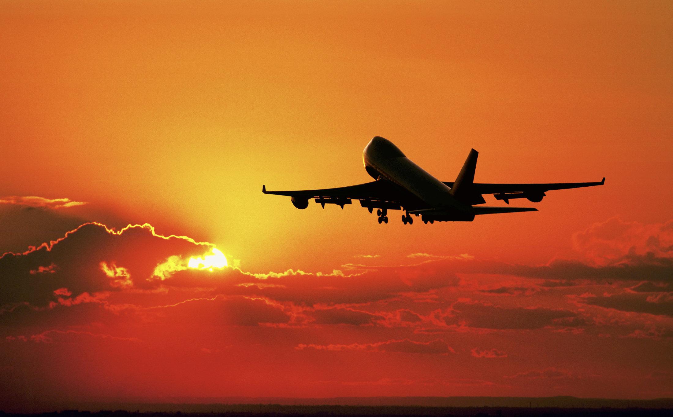 Passenger jet airplane taking off at dusk