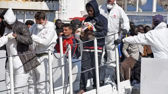 A man holds a baby as migrants and refugees arrive in the port of Messina following a rescue operation at sea by the Italian Coast Guard ship 'Diciotti' on March 17, 2016 in Sicily.  More than 2,400 migrants and three corpses have been recovered from people smugglers' boats off Libya Italy's coastguard said on March 16, 2016. After several quiet weeks, the figures represent a pick-up in the flow of migrants attempting to reach Italy via Libya, a route through which around 330,000 people have made it to Europe since the start of 2014. / AFP / GIOVANNI ISOLINO        (Photo credit should read GIOVANNI ISOLINO/AFP/Getty Images)