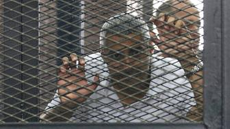 "Mohamed Fahmy stands behind bars as he waits to listen the ruling at a court in Cairo June 23, 2014. Three Al Jazeera journalists were jailed for seven years in Egypt on Monday after a court convicted them of helping a ""terrorist organisation"" by spreading lies, in a case that has raised questions about the country's respect for media freedoms. The three, who all deny the charge, include Australian Peter Greste, Al Jazeera's Kenya-based correspondent, and Canadian-Egyptian national Mohamed Fahmy, Cairo bureau chief of Al Jazeera English. The third defendant, Egyptian producer Baher Mohamed, received an additional three-year jail sentence on a separate charge involving possession of ammunition. REUTERS/Asmaa Waguih   (EGYPT - Tags: POLITICS CIVIL UNREST SOCIETY)"