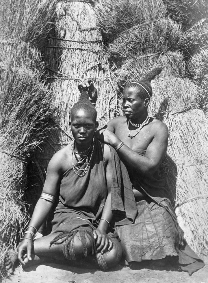 An adult Zulu woman grooms and adorns the hair of a younger woman in South Africa.