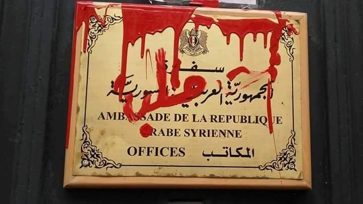 """Demonstrators splash red paint with the word """"Aleppo"""" on a sign at the Syrian Conciliate in Paris, France."""