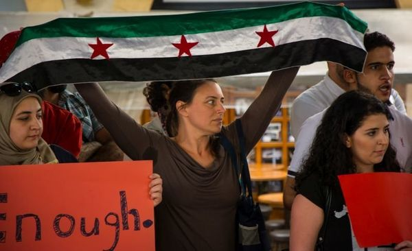 People hold red placards and the Syrian opposition flag in Beirut, Lebanon.