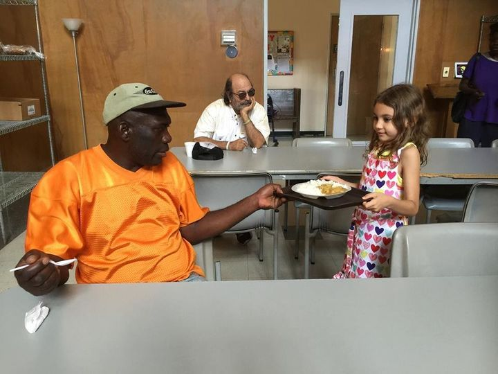 A tiny volunteer from Alabama's Birmingham Islamic Society serves food for National Muslim Soup Kitchen Day.
