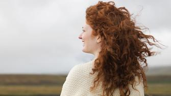 Red hair of Caucasian woman blowing in wind