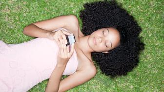 Overhead view of teenage girl laying on grass with cell phone