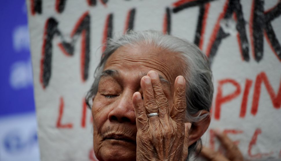 "A Filipina ""comfort woman"" wipes away a tear during a January protest in Manila. Over 1,000 women and girls were capture"
