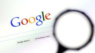 AUCKLAND - AUG 10 2014:Magnifying glass against Google homepage.Google search engine process over one billion search requests and about 24 petabytes of user-generated data each day (as of 2009)