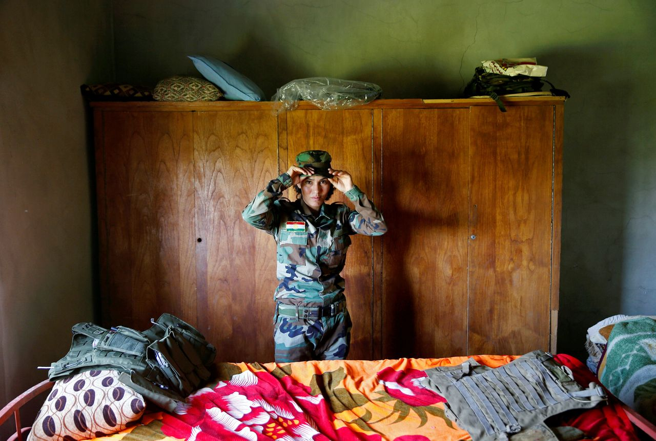 """Dahir adjusts her cap in a bedroom near the front line. """"They took eight of my neighbors and I saw they were killing the children,"""" she said, referring to ISIS militants."""