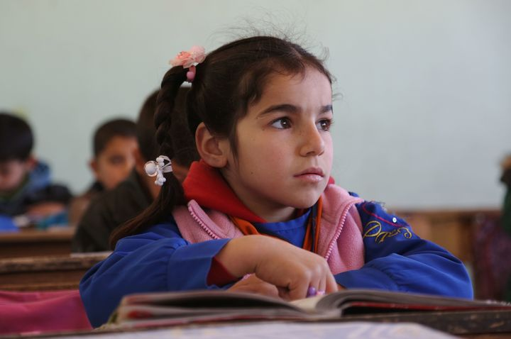 A Kurdish student listens as her teachers speaks during a lesson at the Musa Bin Nusayr school in the northeastern Syrian cit