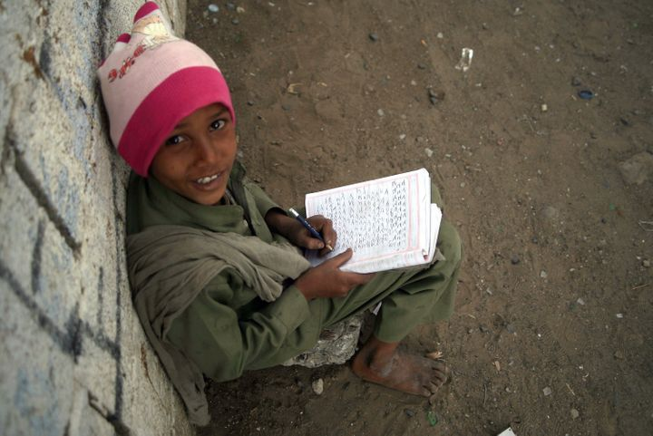 A Yemeni young boy poses as he writes in an exercise book sitting outside a minibus (unseen) turned into a mobile classroom o
