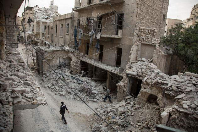A Syrian man walks past destroyed buildings on May 2, 2016, in Aleppo's Bab al-Hadid neighborhood. The...