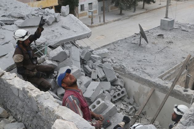 Civil defense members work at a site hit by an airstrike in the rebel held area of Aleppo on Tuesday....