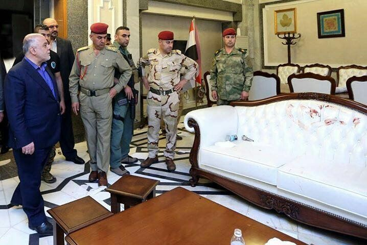 Iraqi Prime Minister Haider al Abadi surveys the damage toa couch in the Iraqi Parliament building after protesters sto